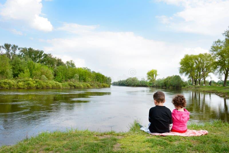 Fratello e sorellina che si siedono sulla banca del fiume. immagini stock