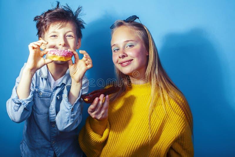 Fratello felice e sorella della famiglia che mangiano le guarnizioni di gomma piuma su fondo blu, cibo di concetto della gente di fotografia stock libera da diritti