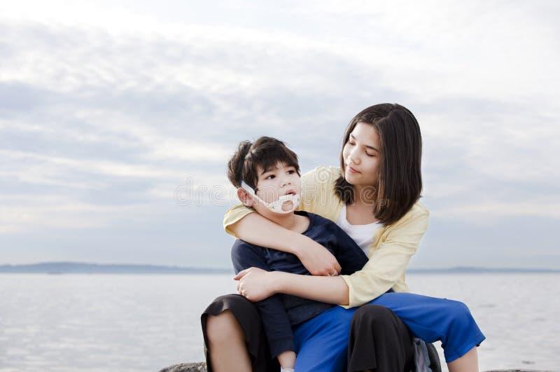 Fratello invalido holding adolescente della sorella fotografia stock