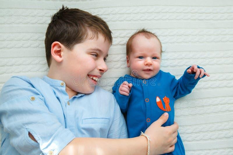 Fratello maggiore che abbraccia la sua ragazza di neonato Bambino del bambino che incontra nuovo fratello germano fotografia stock
