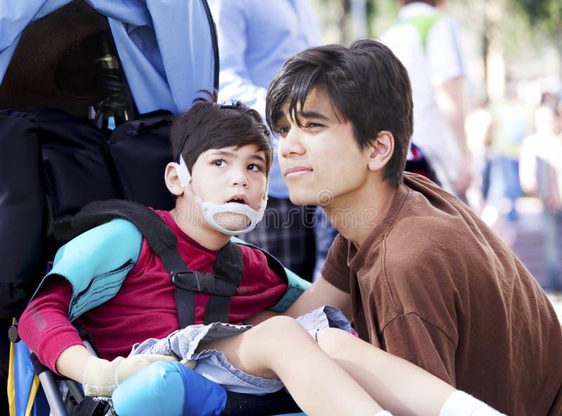 Fratello maggiore che prende cura del ragazzino disabile in sedia a rotelle fotografia stock