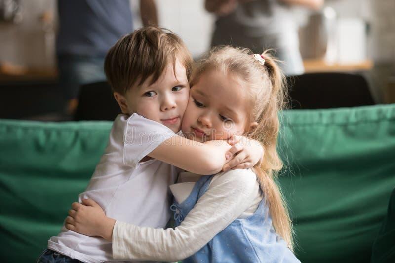 Fratello piccolo che abbraccia sorella turbata che si siede sullo strato fotografia stock libera da diritti