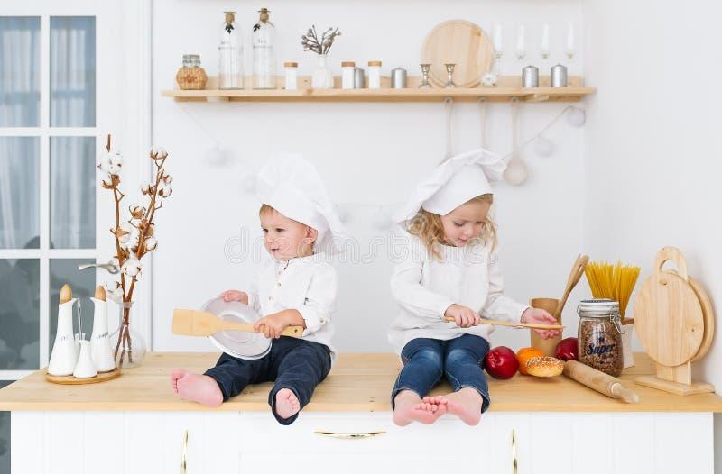 Fratello piccolo e sorella nei cappucci del cuoco che si siedono nella cucina nella casa Gli assistenti della madre fotografia stock libera da diritti