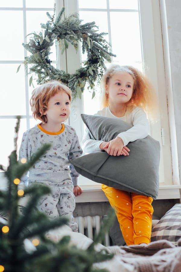 Fratello piccolo e sorella in pigiami sul letto, morni di Natale fotografia stock libera da diritti