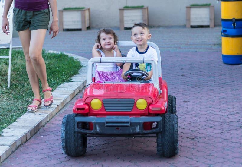Fratello piccolo e sorella sorridenti che guidano in macchina del giocattolo Ritratto dei bambini felici sulla via Bambini svegli fotografia stock