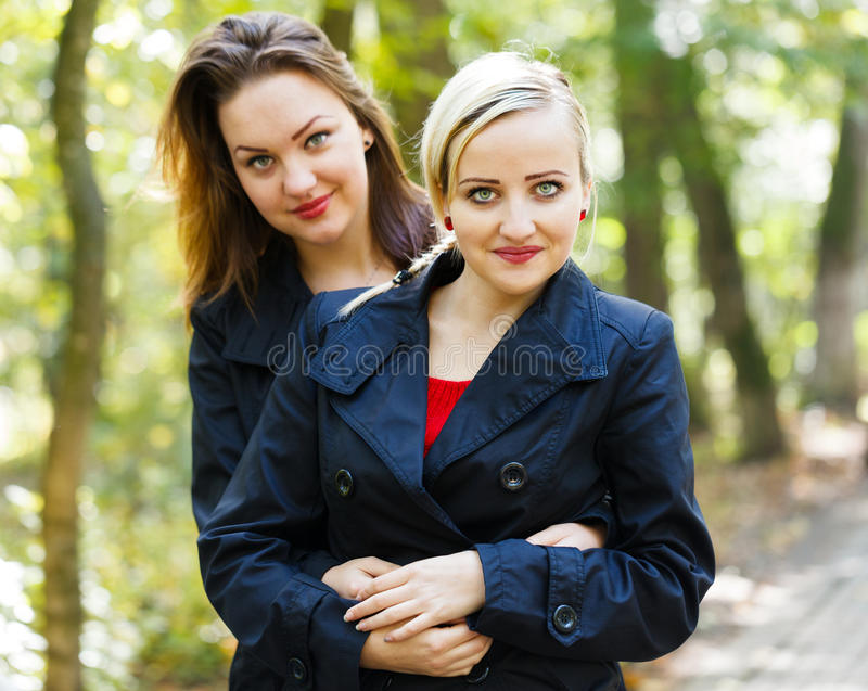 Fraternal Twins - Girls. Beautiful fraternal twins in a park hugging each other stock photos