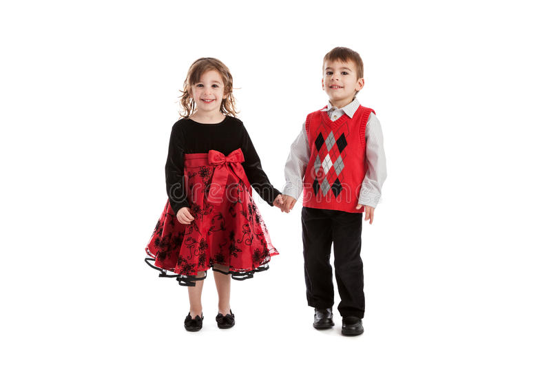 Fraternal twins portrait. Portrait of 3 year old fraternal boy and girl twins wearing holiday outfits isolated on white background royalty free stock photography