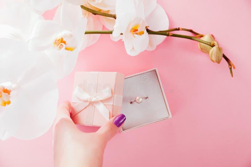 Frau öffnet eine Geschenkbox mit einem silbernen Perlenring, der mit Orchidee umgeben wird angebot stockfoto