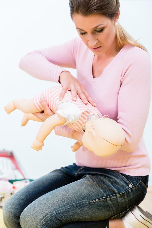 Frau in übender Wiederbelebung des Kurses der ersten Hilfe des Kindes auf Baby d stockfotografie