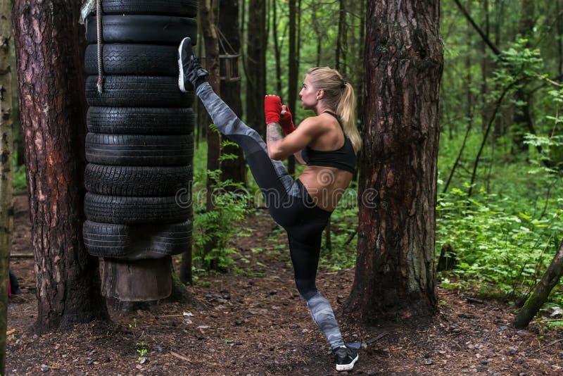 Frau übendes Kickboxing, einen Beinaxttritt durchführend, der draußen ausarbeitet stockfotografie