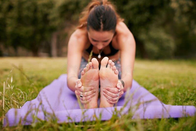 Frau übendes paschimottanasana Yoga draußen lizenzfreie stockbilder