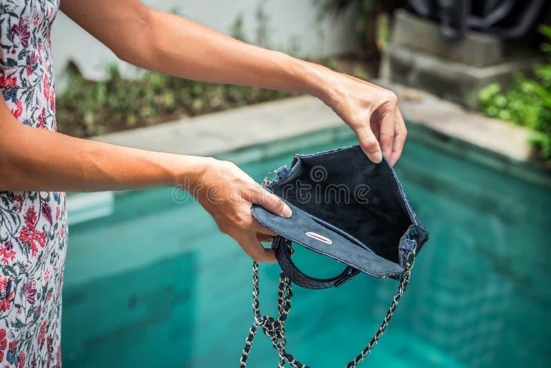 Frau übergibt öffnende leere Luxus-snakeskin Pythonschlangenhandtasche auf einem Swimmingpoolhintergrund lizenzfreie stockbilder