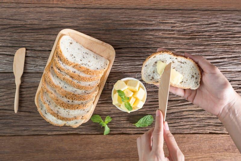 Frau übergibt das Halten der ausgebreiteten Butter des Messers auf Brot stockfoto