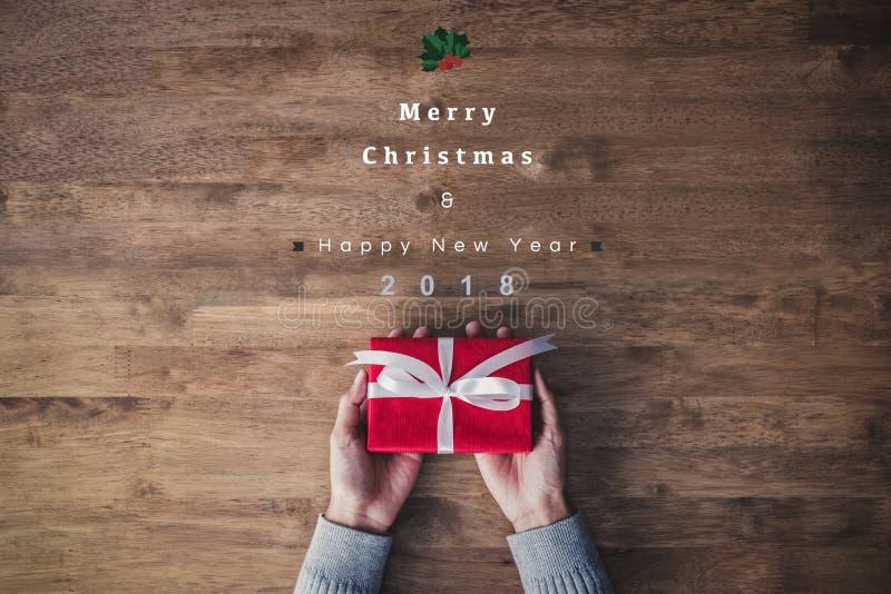 Frau übergibt das Halten der roten Geschenkbox auf einer Tabelle mit Texten der frohen Weihnachten und des guten Rutsch ins Neue  stockbild