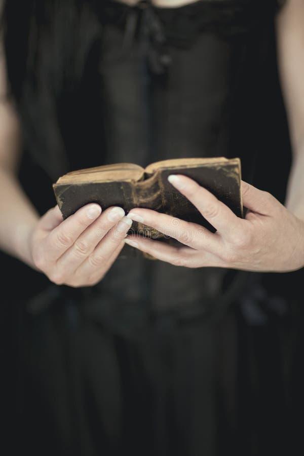 Frau übergibt das Halten der Weinlese altes Buch, sehr dunkle atmosphärische sinnliche ländliche, gotische Atelieraufnahme lizenzfreie stockfotos