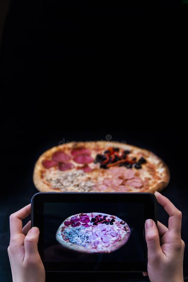 Frau übergibt das Machen von Fotos einer Pizza mit einer Tablette, die auf Schwarzem lokalisiert wird stockfotografie