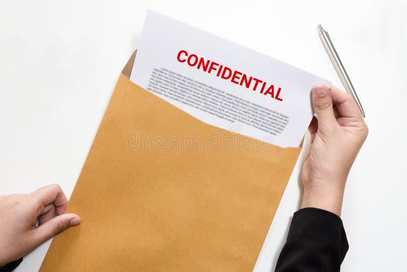 Frau übergibt das Verwahren und das Betrachten des vertraulichen Dokuments im enve stockbilder