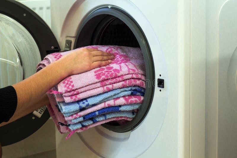 Frau übergibt Wäscherei in Waschmaschine zu Hause setzen lizenzfreies stockfoto