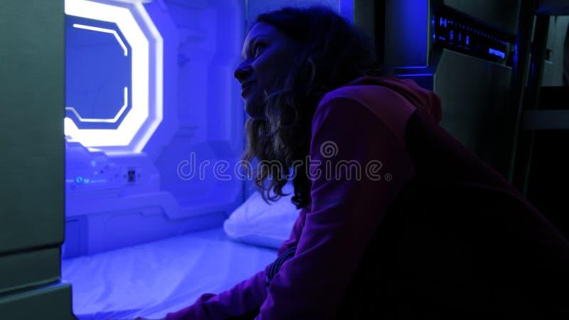 Frau überprüft das Sleepbox mit Neonlichtern, einen Raumkapselbehälter für das Schlafen am Flughafen lizenzfreie stockfotos