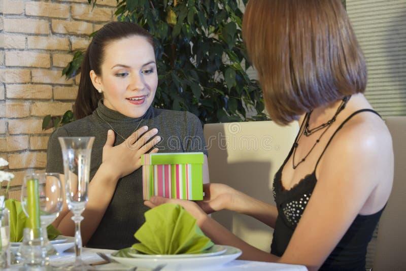 Frau überraschend mit einem Geschenk lizenzfreie stockbilder