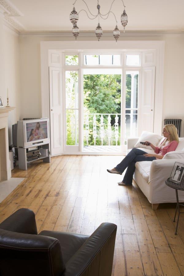 Frau in überwachendem Fernsehen des Wohnzimmers stockbilder