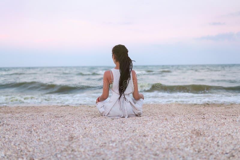 Frau übt Yoga und meditiert im Lotussitz auf dem Strand stockfoto