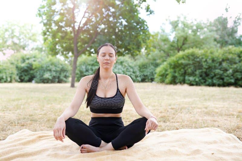 Frau übt Yoga und meditiert im Lotussitz, Naturhintergrund mit Kopienraum lizenzfreie stockfotos
