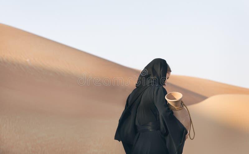 Frau in abaya traditionellem emirati Kleid in einer Wüste mit Wasserteller stockfotos