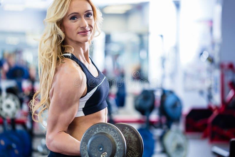 Frau an anhebenden Gewichten des Bodybuilding in der Turnhalle lizenzfreie stockbilder
