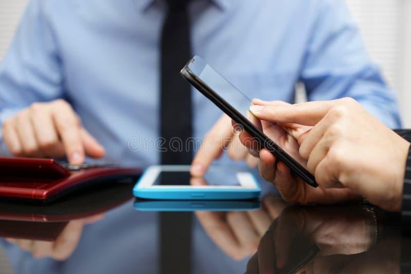 Frau arbeitet an Handy und Geschäftsmann in Hintergrund c stockfotos