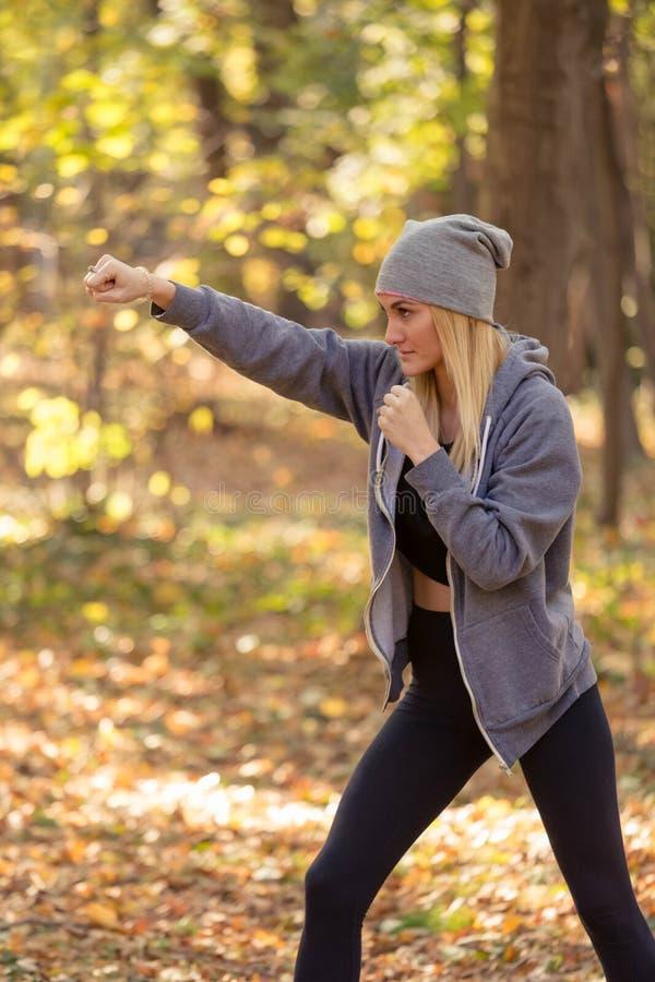 Frau arbeitet, um das Kickboxen zu üben und drückt Angriff aus lizenzfreie stockfotos