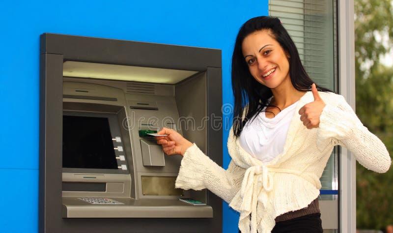 Frau an ATM lizenzfreie stockbilder