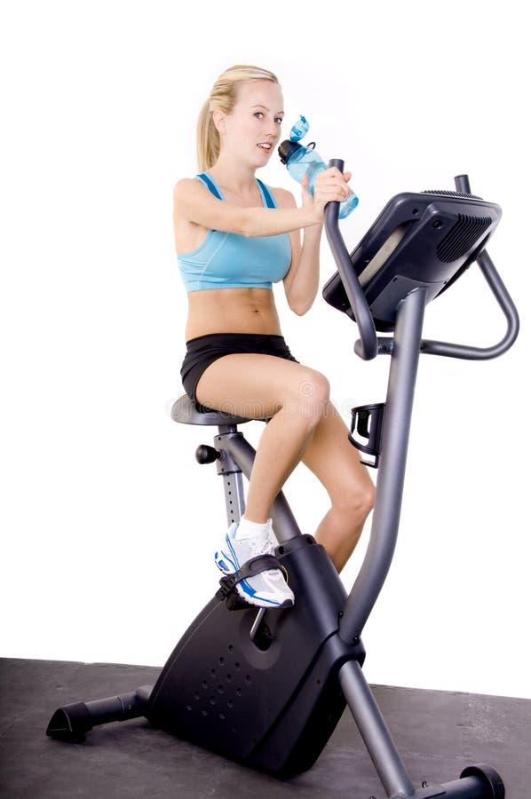 Frau auf Übungs-Fahrrad lizenzfreie stockbilder