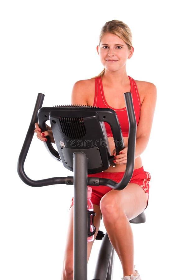 Frau auf Übungs-Fahrrad lizenzfreie stockfotos