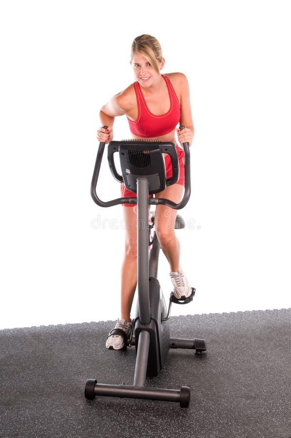 Frau auf Übungs-Fahrrad stockfotos