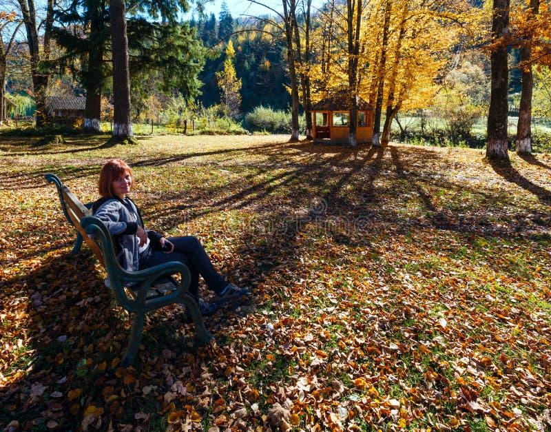 Frau auf Bank im Herbstkarpatengebirgssonnigen Park auf Fluss lizenzfreies stockbild