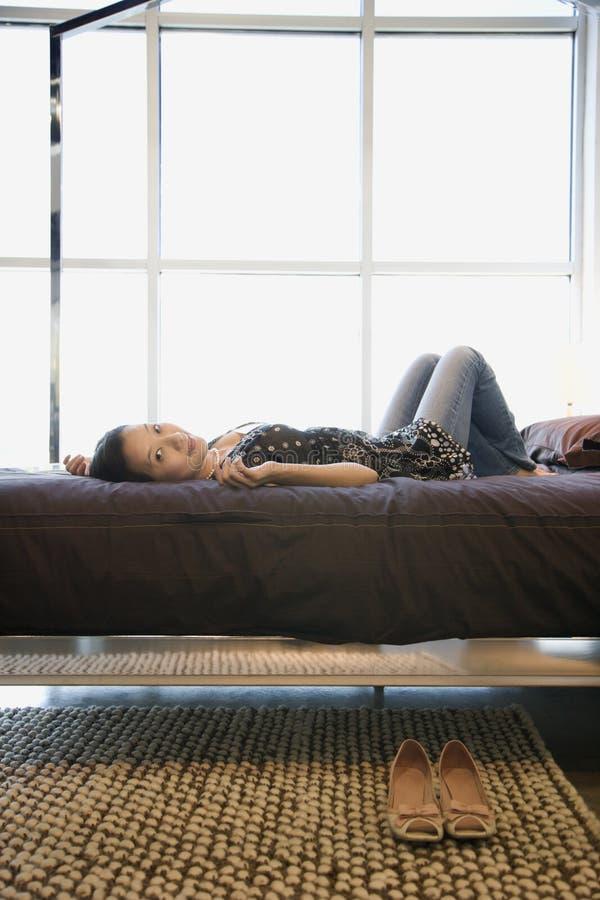 Frau auf Bett. stockbilder