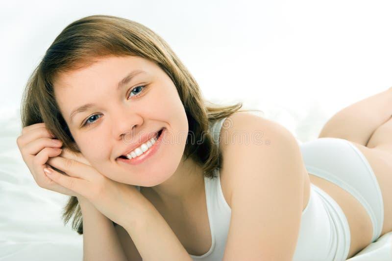 Frau auf Bett lizenzfreie stockbilder