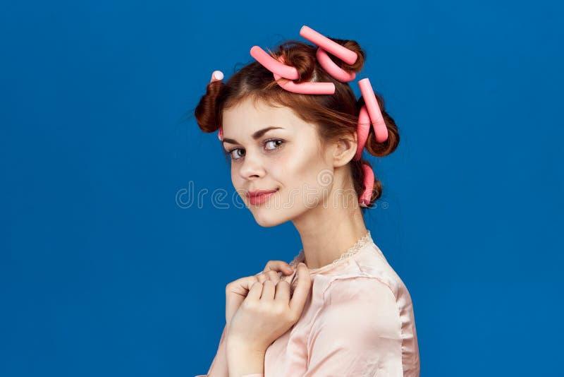 Frau auf blauem Hintergrund, Hausfrau, Frisur, Haarlockenwickler, Porträt lizenzfreie stockfotos