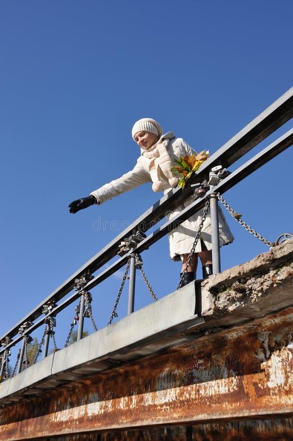 Frau auf Brücke wirft Ahornblatt im Wasser lizenzfreie stockfotografie