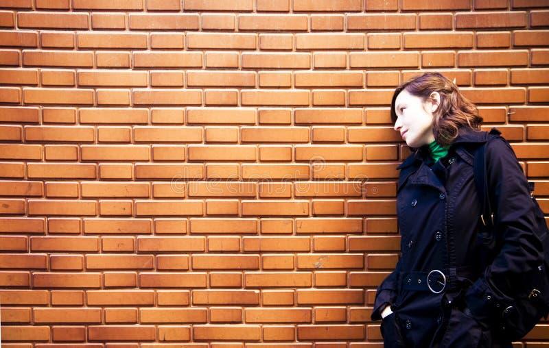 Frau auf brickwall stockfotografie