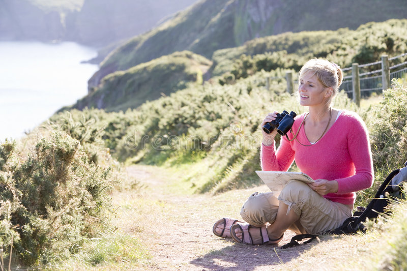 Frau auf cliffside Pfad unter Verwendung der Binokel lizenzfreie stockfotografie