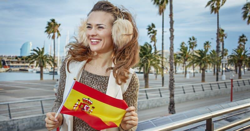 Frau auf Damm mit der spanischen Flagge, die Abstand untersucht lizenzfreies stockfoto