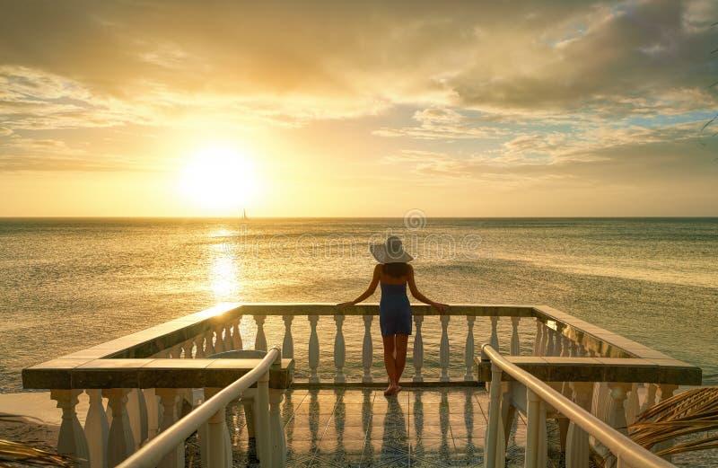 Frau auf dem Balkon, der den schönen Sonnenuntergang betrachtet stockbilder