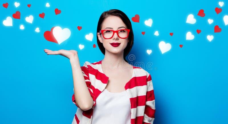 Frau auf dem blauen Hintergrund mit Herzen lizenzfreies stockbild