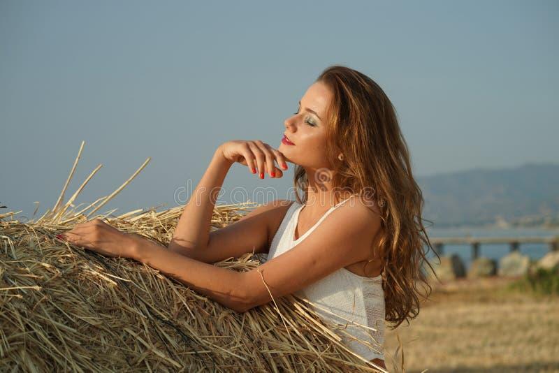 Frau auf dem Gebiet durch den Sonnenuntergang lizenzfreie stockbilder