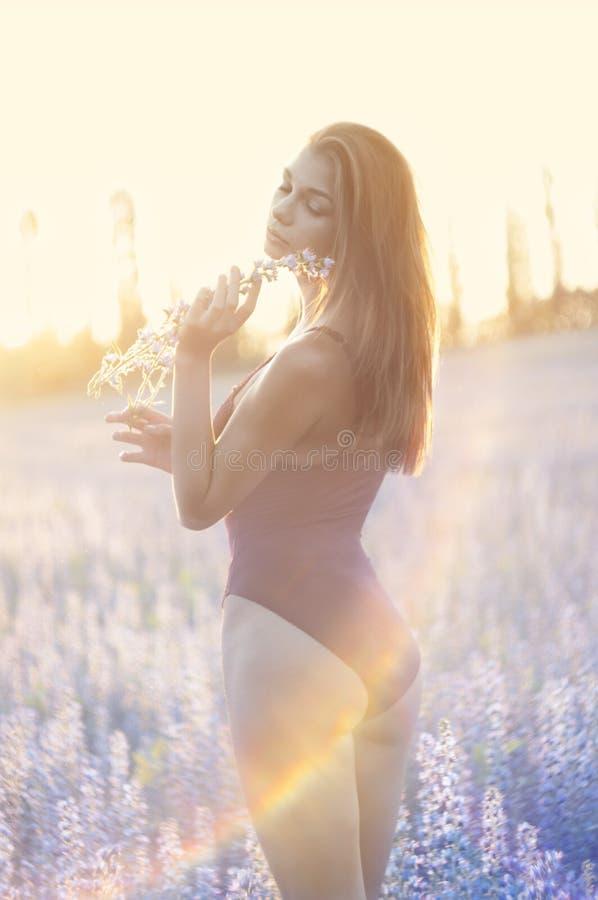 Frau auf dem Gebiet mit Blume am Sommersonnenuntergang. lizenzfreie stockbilder