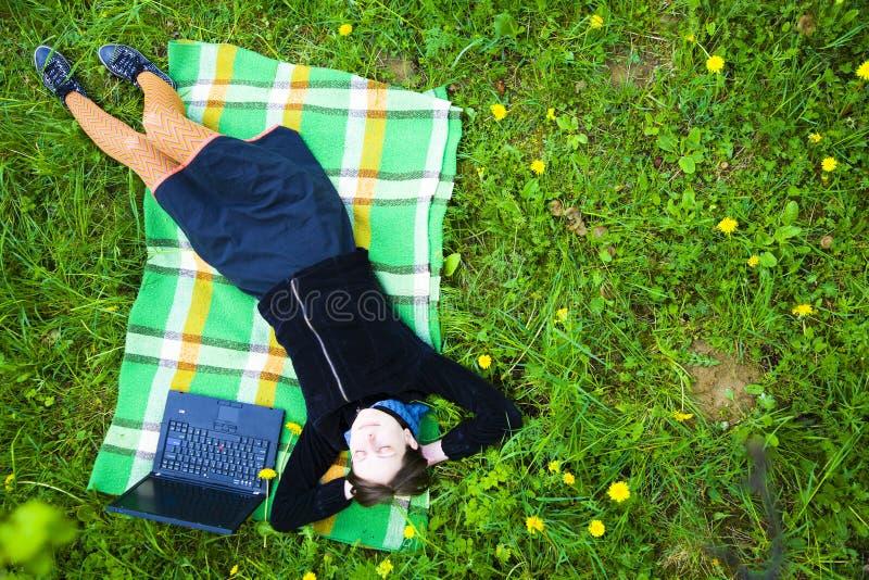 Frau auf dem Gebiet mit Laptop stockbild