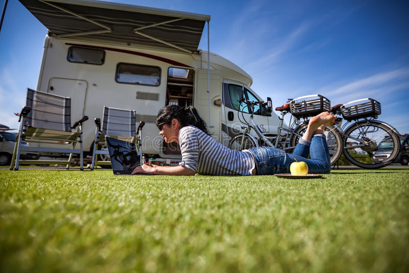 Frau auf dem Gras, den Laptop betrachtend nahe dem campe stockfoto