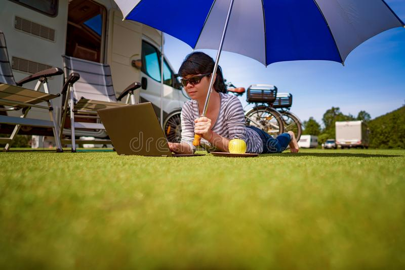 Frau auf dem Gras, den Laptop betrachtend unter Regenschirm nahe Th lizenzfreie stockbilder
